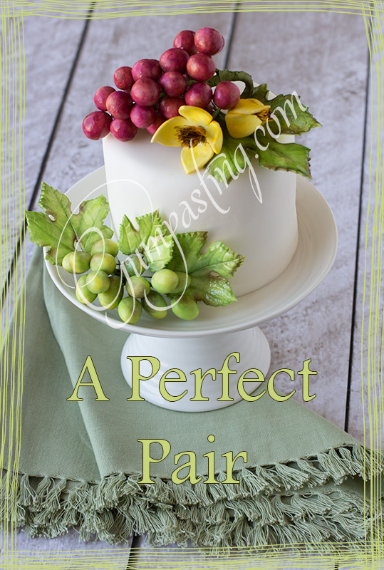 {A Cake Decorated With a Combination of Red & Green Gumpaste Grape Bunches and Yellow Clematis Flowers}